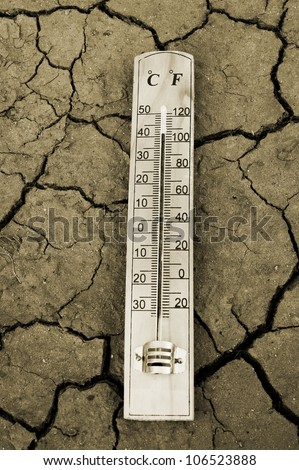 Thermometer on dry soil close up - stock photo