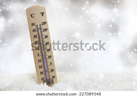 Thermometer on snow shows low temperatures - stock photo