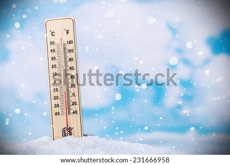 Thermometer on snow shows low temperatures on the sky background with clouds - stock photo
