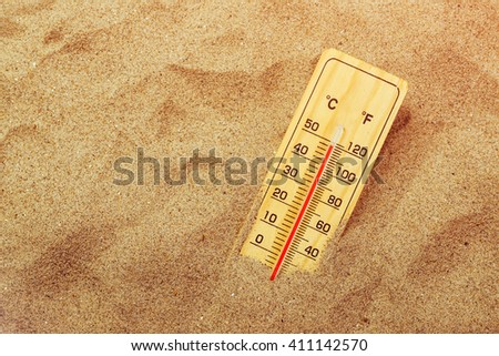 Thermometer with celsius and farenheit scale on warm beach sand showing record extreme high temperatures - stock photo