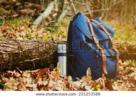 Thermos and backpack outdoors on autumn nature, hiking theme - stock photo