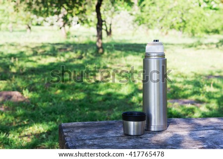 Thermos  and cup of coffee on wooden table with nature on background. Tourism and travel - stock photo