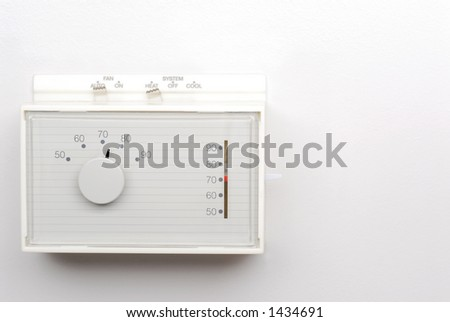 Thermostat on White Wall with Space for Text - stock photo
