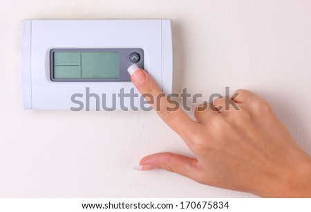 thermostat. woman's hand turn off the room temperature on a modern programmable digital  wall heater. closeup  - stock photo