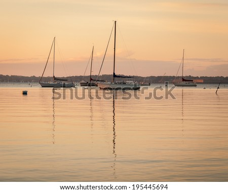 These are several sailboats at anchor near Jamestown, Rhode Island in Narragansett Bay. Fort Adams is seen in the distant background. / Sailboats at Sunrise, Jamestown, RI. - stock photo