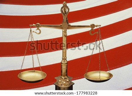 These are the golden Scales of Justice set against a background of the red and white stripes of the American flag. The scales are in a balanced position. This is a digitally created image. - stock photo