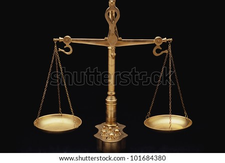 These are the golden scales of justice. They represent the legal systems and courts. These scales are shown in perfect balance against a black background. - stock photo