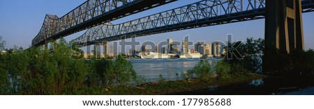 These are the Twin Bridges to New Orleans along the Mississippi River. In the background is the skyline in morning light. - stock photo