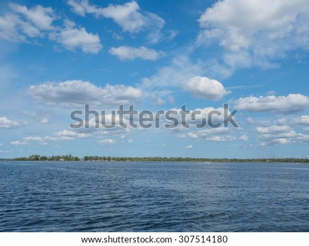 These is n image of clouds over blue water at East Gull Lake in Minnesota. - stock photo