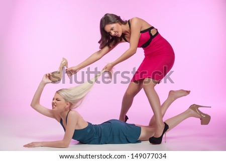 These shoes are mine!  Two angry young women fighting for the shoes while isolated on pink background - stock photo