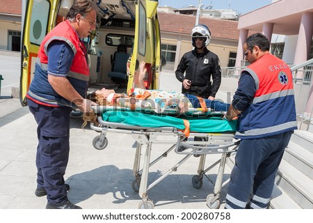 THESSALONIKI, GREECE- APRIL 24, 2013: Emergency team assisting injured teacher during during an earthquake exercise at 6th primary school in Thessaloniki, Greece.