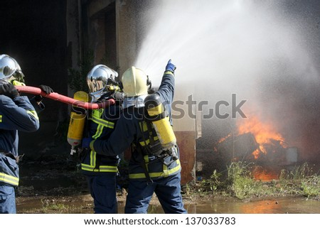THESSALONIKI, GREECE - APRIL 19:Firefighter fighting for a fire attack, during a training exercise for the consequences earthquake in industrial area of Sindos on April 19,2013 in Thessaloniki, Greece