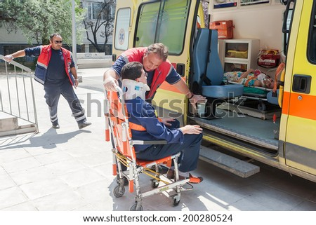 THESSALONIKI, GREECE- APRIL 24, 2013: Paramedic assisting injured teacher, getting in the ambulance, during an earthquake exercise at 6th primary school in Thessaloniki, Greece. - stock photo