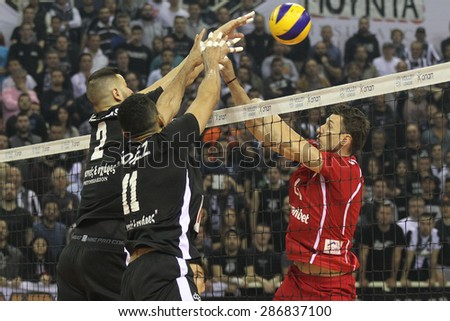 THESSALONIKI, GREECE, APRIL 23, 2015: Players in action on the net during the Hellenic Volleyball League final games Paok vs Olympiacos at PAOK Sports Arena. - stock photo