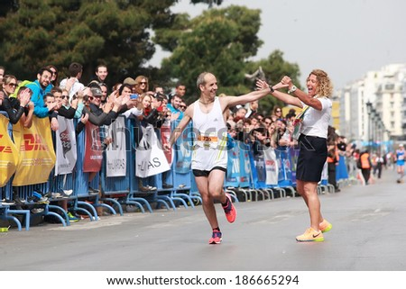 THESSALONIKI, GREECE - APRIL 6, 2014 : Runner SIKALOS GEORGIOS finishing proudly in the 9th Marathon Alexander the Great. The marathon is an annual event. - stock photo