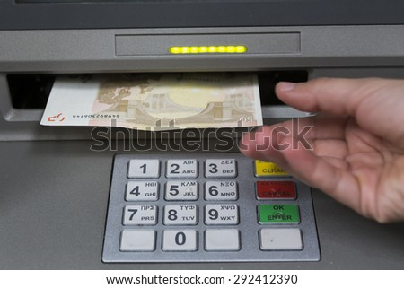 THESSALONIKI, GREECE,JUN 27 2015: People stand in a queue to use the ATMs of a bank. Person receiving money from the ATM. - stock photo
