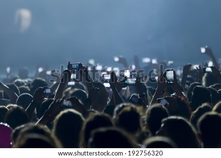 THESSALONIKI, GREECE, MAY 8 2014:People taking photographs with touch smart phone during a music concert live on stage for the Ace of Heart tour at Sports arena in Thessaloniki. - stock photo