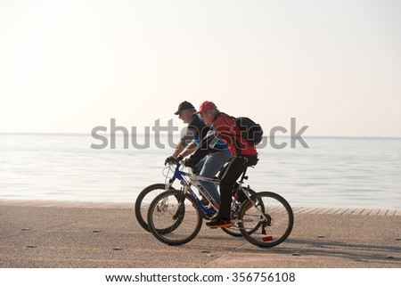 Thessaloniki, Greece - November 17, 2015: Two bikers enjoying their day by the beach while riding their bikes on a sunny day in Thessaloniki Greece