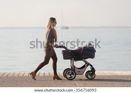 Thessaloniki, Greece - November 17, 2015: Woman is enjoying her day by taking her baby for a walk on a beautiful sunny day by the beach in Thessaloniki Greece
