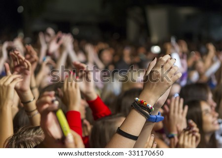 THESSALONIKI, GREECE, SEPTEMBER 13, 2013: Cheering crowd standing with raised hands up and clapping at music concert.