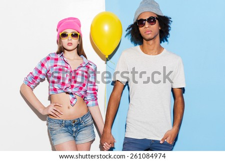 They are cool! Funky young couple holding yellow balloon and looking at camera while standing against colorful background - stock photo