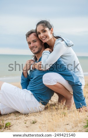 They are sitting in the sand in casual clothes, looking at the camera - stock photo