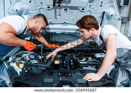 two handsome car mechanics in uniform checking the engine under hood