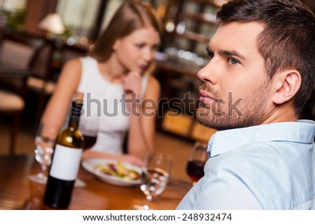 They have nothing more to say. Frustrated young man looking away while sitting together with his girlfriend in restaurant  - stock photo