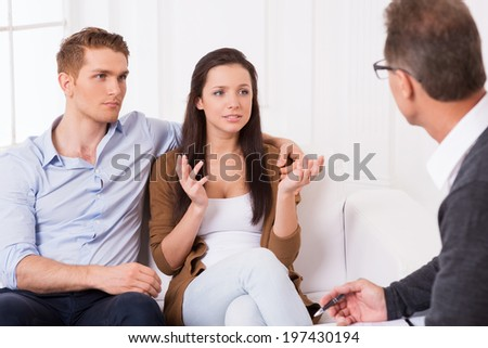They need an expert advice. Frustrated young couple telling about their relationship problems to psychiatrist  - stock photo
