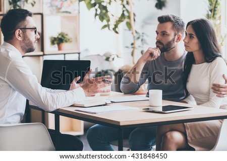 They need an expert advice. Young couple sitting together at the desk and listening to their financial advisor  - stock photo
