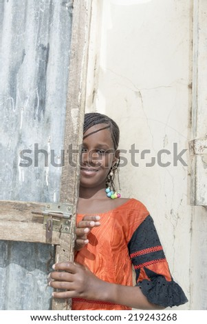 Thiaroye, Senegal, Africa - July 30, 2014: Unidentified girl partially hiding behind a door (traditional hairstyle) in the popular district of Guinaw Rails - stock photo