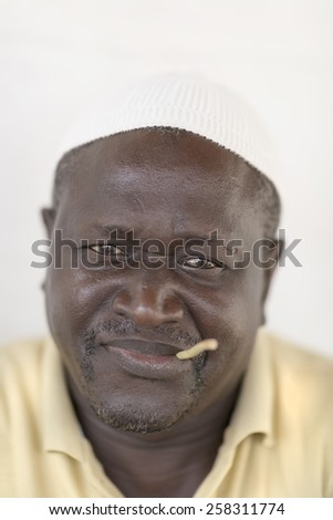 Thiaroye, Senegal, Africa  July 18, 2014: Unidentified Muslim men sitting  in front of his house and chewing a miswak (teeth cleaning twig) - stock photo