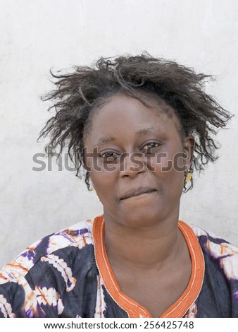 THIAROYE, SENEGAL, AFRICA, JULY 18, 2014, Unidentified woman sitting in front of a street wall - stock photo