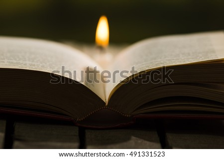 Thick book lying open on wooden surface, wax candle sitting next to it, beautiful night light setting, magic concept shoot