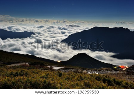 Thick clouds are covering between mountain ranges as seen from above. - stock photo