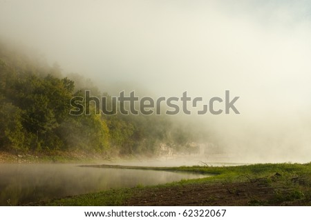 Thick fog covering beaver lake, Arkansas after a couple days of heavy rainfall. - stock photo