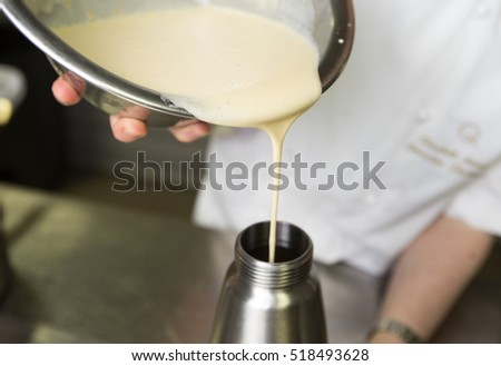 Thick fresh sweet dessert cream, being poured into a metal container in an industrial kitchen.