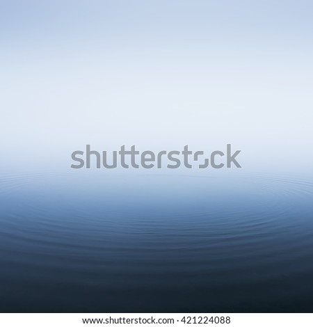 Thick morning fog on the lake. Circles on the water - stock photo