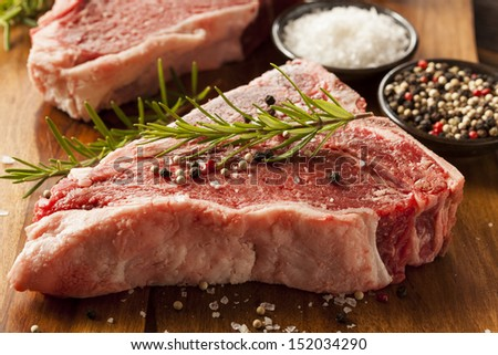 Thick Raw T-Bone Steak with Seasoning and Rosemary - stock photo