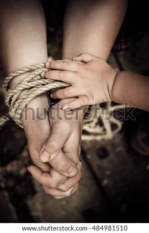 Thick rope ties the hands of women. Child's hand holding a rope.