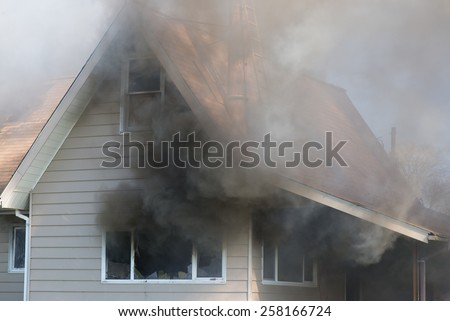 Thick smoke engulfs a home, foreshadowing the blazing destruction to come. - stock photo
