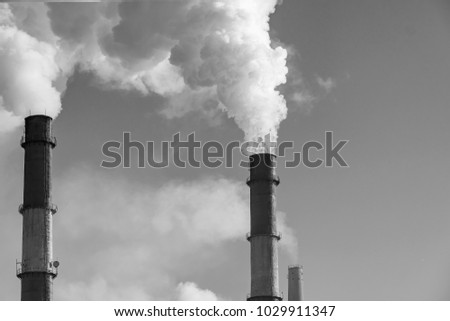 Thick smoke from factory chimneys on a sky background. Black and white photo