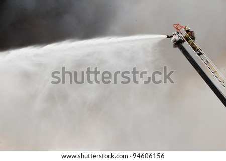 Thick smoke provides a dramtic background as a high tech fire truck uses it's ladder to direct thousands of gallons of water onto the roof of a blazing house fire. - stock photo