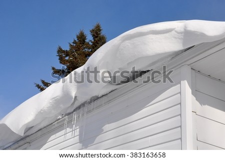 Thick snow hanging on the roof - stock photo