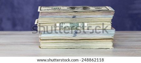 Thick stack of US cash. The stack of US cash in mixed notes of different colors and tones, positioned on the wooden table - stock photo