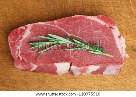 Thick trimmed sirloin beef steak on wooden food preparation board. - stock photo