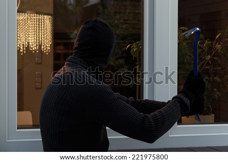 Thief breaks the glass with a crowbar - stock photo