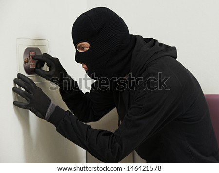 Thief burglar during home safe codebreaking - stock photo
