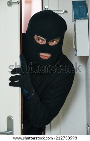 Thief burglar opening door during house breaking penetration - stock photo