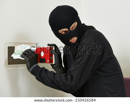 Thief burglar stealing euro money during home safe codebreaking - stock photo